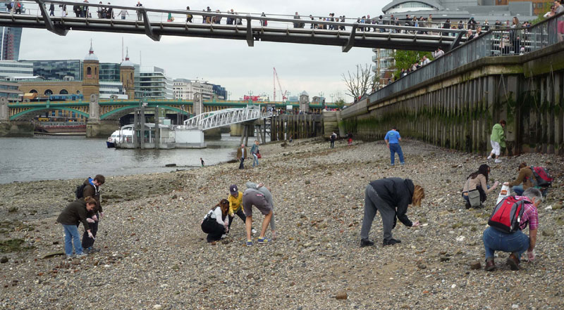 Amateur sleuths look for historical artefacts on the rocky foreshore of London's River Thames at low tide