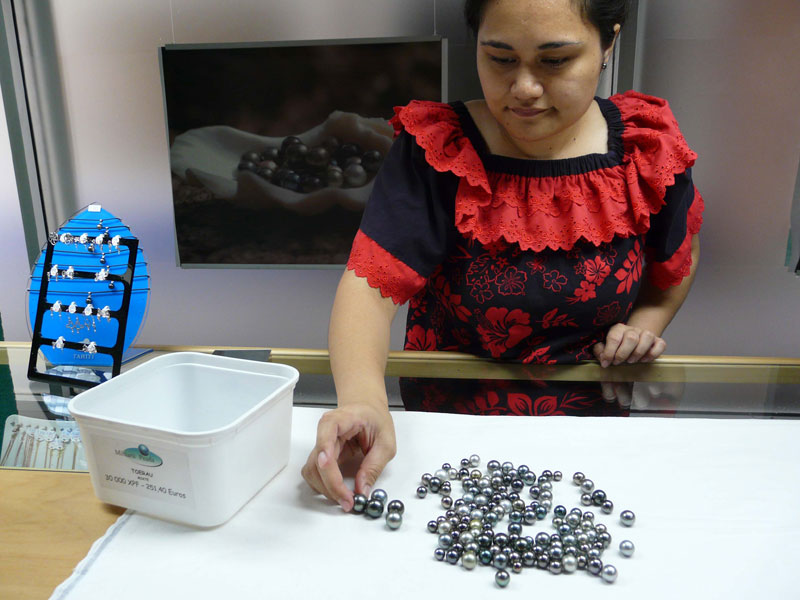 Manager of the Mihiarii shop in Papeete with a tubful of black pearls