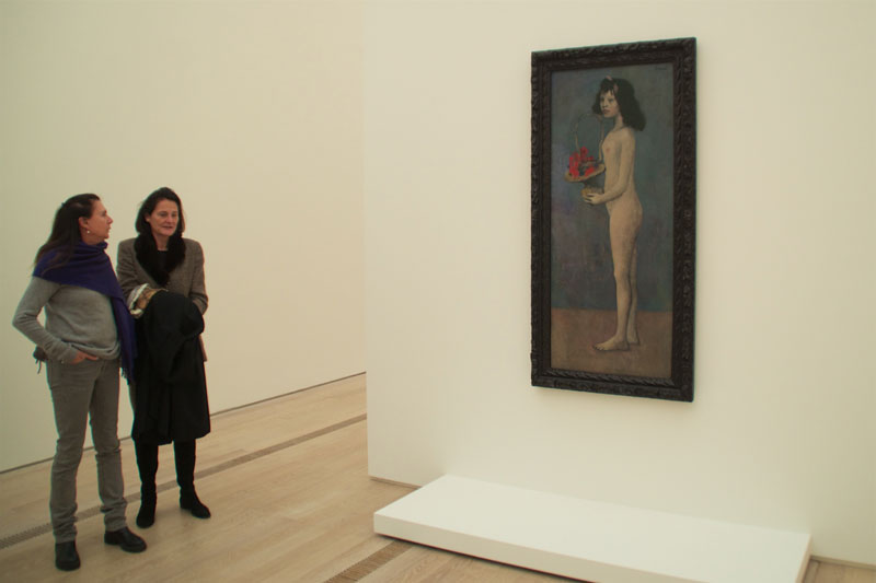 Visitors to Fondation Beyeler's exhibition The Young Picasso—Blue and Rose Periods, stand in front of Fillette à la corbeille fleurie